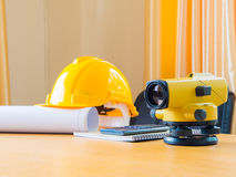 Theodolite and construction helmet, rolls and plans. on the desk. Construction industry concept. Royalty Free Stock Image