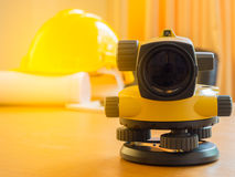 Theodolite and construction helmet, rolls and plans. on the desk. Construction industry concept. Stock Photography