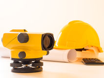 Theodolite and construction helmet, rolls and plans. on white background. Stock Images