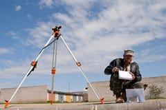 Theodolite em um tripé com trabalhador da construção Foto de Stock