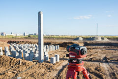 Theodolite in front of piles field Royalty Free Stock Photography