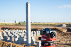 Theodolite in front of piles field Royalty Free Stock Photo