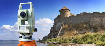 Theodolite survey outdoors. Near medieval citadel Royalty Free Stock Photos