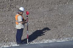 Theodolite technician. In a road Stock Image