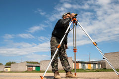 Theodolite on a tripod with construction worker. Surveyor measuring land for construction stock photo