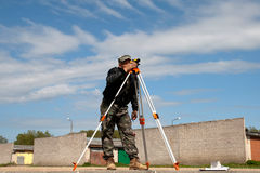 Theodolite on a tripod with construction worker. Surveyor measuring land for new street build royalty free stock image