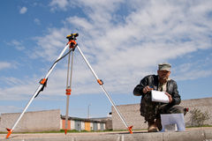 Theodolite on a tripod with construction worker. Surveyor measuring land for new street build Stock Photo