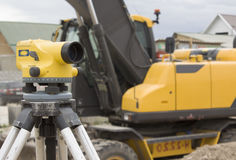 Theodolite on tripod. Theodolite on a tripod on a road construction site in the background of the excavator Stock Image