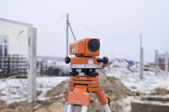 Theodolite on a tripod, set on a construction site. At the construction site for work on the layout object under construction is used optical measuring Royalty Free Stock Photos