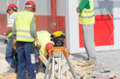 Theodolite and workers at construction site Stock Photos