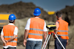 Theodolite and workers at construction site Stock Image