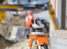 Theodolite and workers at construction site Royalty Free Stock Photography