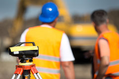 Theodolite and workers at construction site Royalty Free Stock Photos