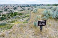 Theodore Roosevelt parka narodowego badlands sceneria blisko Medora, Północny Dakota w lecie - znak ostrzega niestała ziemia wyci fotografia stock