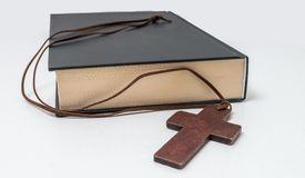 Theology concept. Bible book and brown crucifix on necklace Royalty Free Stock Images