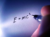 Theory of Relativity. E = MC2, the theory of relativity written in black pen on blue surface, hand holding pen royalty free stock image