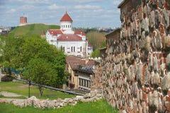 对Theotokos的大教堂的看法和Gediminas耸立与中世纪城市墙壁在前景在维尔纽斯,立陶宛 免版税图库摄影