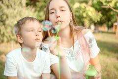 Ther e bolhas de sabão de sopro da irmã fotografia de stock