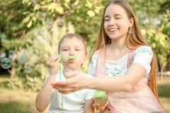 Ther e bolhas de sabão de sopro da irmã fotografia de stock royalty free