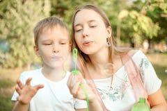 Ther e bolhas de sabão de sopro da irmã imagem de stock royalty free