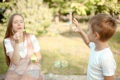 Ther e bolhas de sabão de sopro da irmã imagens de stock royalty free