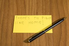 Ther`s no place like home handwrite on a yellow paper with a pen. Composition Stock Photography