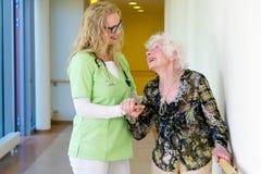 Therapeut Assisting Elderly Walking in het Ziekenhuis stock fotografie