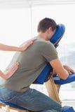 Therapeut, der dem Mann im Krankenhaus Rückenmassage gibt Stockbilder