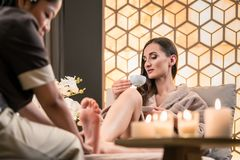 Therapeut, der den Fuß eines weiblichen Kunden in der asiatischen Schönheitsmitte massiert Stockbilder