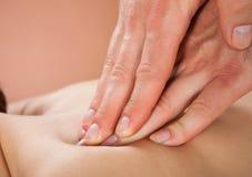 Therapeut, der die Rückseite des weiblichen Kunden am Badekurort massiert lizenzfreies stockfoto