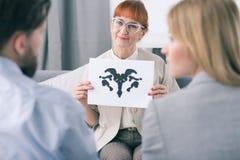 Therapeut, der einen Tintenklekstest mit ihren Patienten durchführt stockbilder