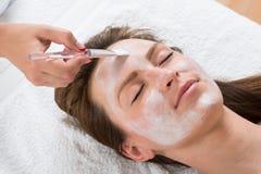 Therapeut, der Gesichtsmaske an der Frau anwendet Stockbilder