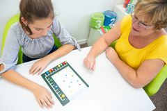 Therapeut, der mit einer Jugendlichen mit Lernschwierigkeiten arbeitet, um logische Tests zu beherrschen lizenzfreie stockfotos