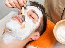 Therapeut die een gezichtsmasker toepassen op een mooie jonge mens in een kuuroord Stock Foto's