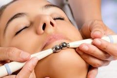 Therapeut die galvanische elektroden met lage frekwentie op gezicht toepassen stock afbeeldingen