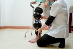 therapeut die geduldige vrouw bijstaan om te lopen gebruikend riet stock foto