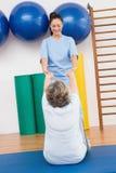 Therapeut die met hogere vrouw aan oefeningsmat werken Stock Afbeelding