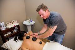 Therapeut die stenen en massage in schoonheidssalon gebruiken stock fotografie