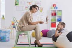 Therapeut die tekening tonen aan jongen stock fotografie
