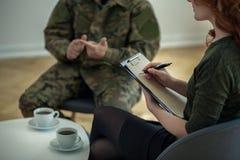 Therapeut het nemen neemt van terwijl het analyseren van gedrag van militair met oorlogssyndroom nota stock afbeelding