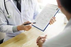 Therapeut het raadplegen aan geduldige mannelijke patiënt die over pillen zijn medische voorschriftdrug in het bureau schrijven royalty-vrije stock afbeelding