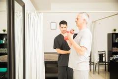 Therapeut-Looking At Mature-Mann-anhebende Dummköpfe in der Klinik lizenzfreie stockfotografie
