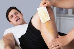 Therapeut-Waxing Man-` s Bein mit Wachs-Streifen stockbild