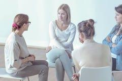 Therapeut, welche jungen Frauen während der Sitzung des Stützungskonsortiums hilft lizenzfreies stockbild