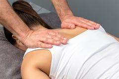 Therapeuthanden die druk op vrouwelijke schouderbladen toepassen royalty-vrije stock afbeeldingen