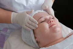Therapeutic and cosmetological facial massage of a fat woman. The hands of a professional beautician in white medical gloves. Therapeutic and cosmetological stock photo