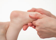 Therapeutic massage for a baby's feet Stock Photos