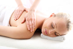 Therapeutic massage, heals the pain and relaxes. Attractive blonde woman in the office spa, relaxes waiting for a cosmetic procedure stock photography