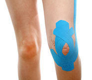 Therapeutic treatment of leg with blue physio tape Stock Photography