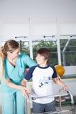 Therapeutvrouw met jongen in rehab Stock Fotografie